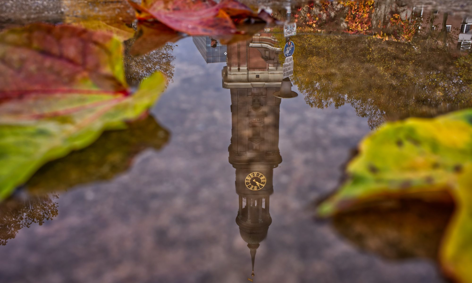Clock tower reflecting on the water; St. Michaelis, Hamburg, Germany